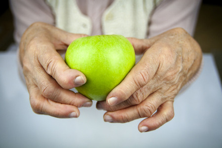Rheumatoid arthritis hands and fruits. Apple in hand photo