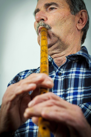 woodwind instrument: Senior man playing pipe Stock Photo