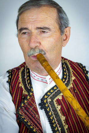 woodwind instrument: Pipe player in traditional clothing. Woodwind instrument Stock Photo