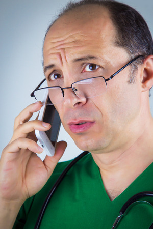 nack: Doctor talking on cell phone. Stetoscope on his nack. Wearing green uniform and glasses