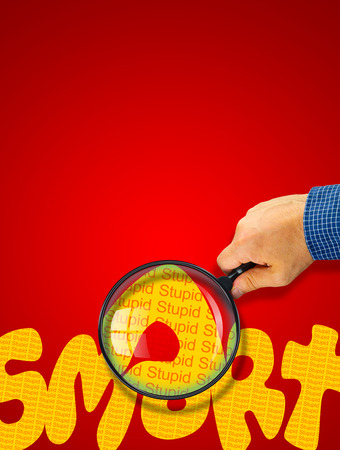 ironic: Human hand holding magnifying glass reading the word SMART hiding the opposite message STUPID. Orange word on a red background. Antonym, hidden reality concept, Hidden message