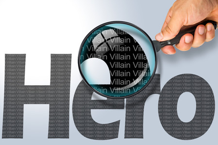 reading glass: Human hand holding magnifying glass reading the word HERO hiding the opposite message VILLAIN. Grey word on a white background. Antonym, hidden reality concept, Hidden message Stock Photo
