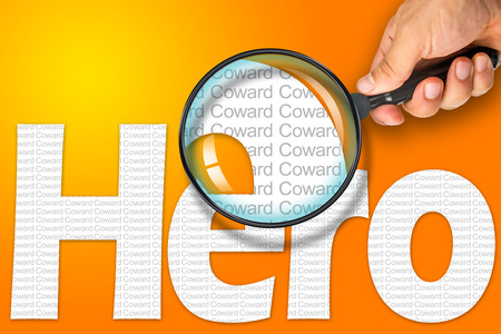 reading glass: Human hand holding magnifying glass reading the word HERO hiding the opposite message COWARD. White word on a orange background. Antonym, hidden reality concept, Hidden message Stock Photo