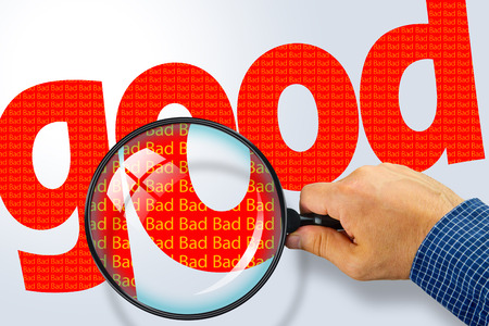 ironic: Human hand holding magnifying glass reading the word GOOD hiding the opposite message BAD. Red word on a white background. Antonym, hidden reality concept, Hidden message Stock Photo