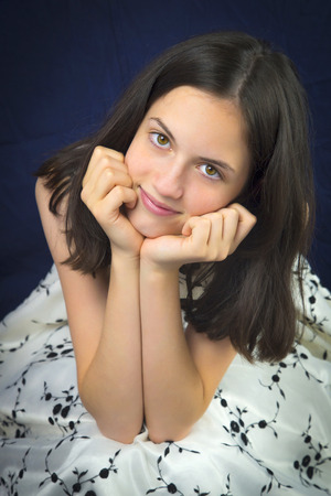 chin on hands: Portrait of beautiful teenage girl smiling. Hands on chin. Well dressed. Dark background
