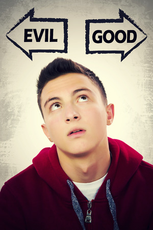 good looking teenage guy: Portrait of handsome teenage boy thinking what to choose between GOOD and EVIL. Grunge background. Pointing arrows