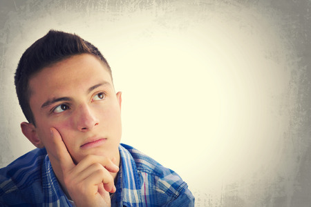 Portrait of handsome teenage boy thinking and looking up to empty space. Grunge background Standard-Bild