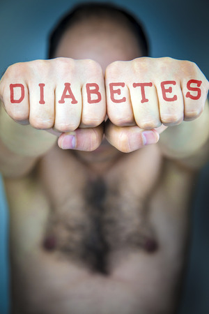strong message: The word DIABETES written on the fists of a man. Fight diabetes medical concept. Male torso.