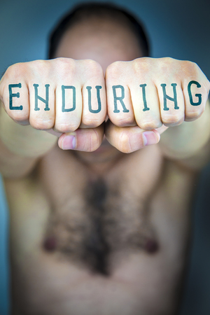 enduring: The word ENDURING written on the fists of a man. Male torso. Dont give up concept