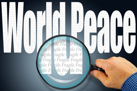 fragile peace: The words WORLD PEACE under observation with magnifying glass showing the word FRAGILE. Anti-war concept. Peace concern concept