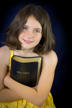 holy bible: Portrait of beautiful little girl holding Holy Bible. Closed bible