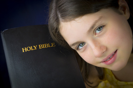 Portrait of beautiful little girl holding Holy Bible. Closed bible
