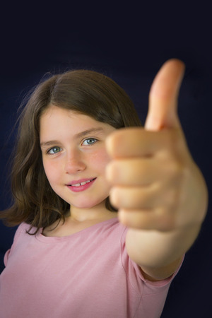 ok: Portrait of beautiful little girl showing ok sign. Copy space. Dark blue background Stock Photo