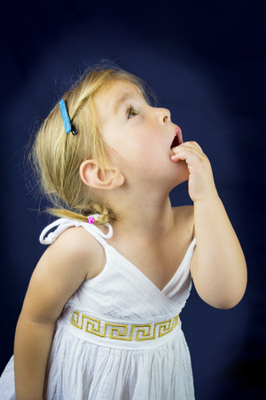 girl looking up: Beautiful little girl with blond hair. Studio shot. Blue background Stock Photo