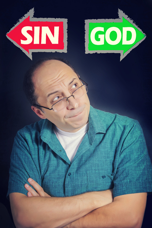 sin: Portrait ofAdult man thinking what to choose between SIN and GOD. Red and green arrows Stock Photo