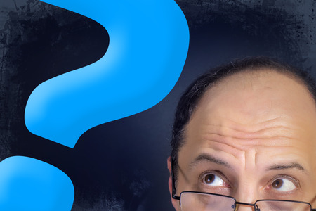 hesitation: Man with bulging eyes looking to big blue question mark expressing dilemma and hesitation. Grunge background.