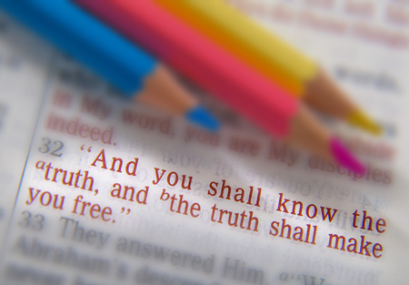 emphasize: And you shall know the truth, and the truth shall make you free. Bible text from John 8:32, the Bible. Blue, red and yellow crayons. Visual effects to emphasize the message. Macro