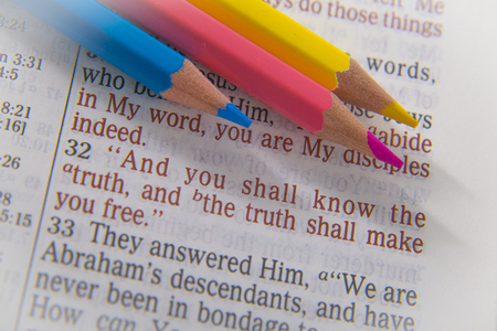 discipleship: And you shall know the truth, and the truth shall make you free. Bible text from John 8:32, the Bible. Blue, red and yellow crayons. Visual effects to emphasize the message. Macro