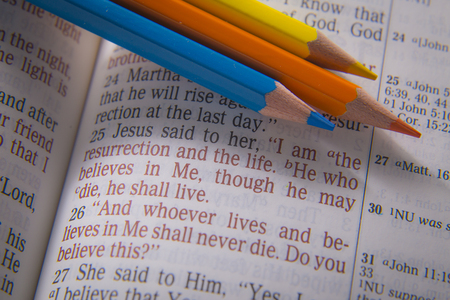 believes: I am the resurrection and the life. He who believes in Me, though he may die, he shall live Bible text from John 11:25, the Bible. Visual effects to emphasize the message. Macro Stock Photo