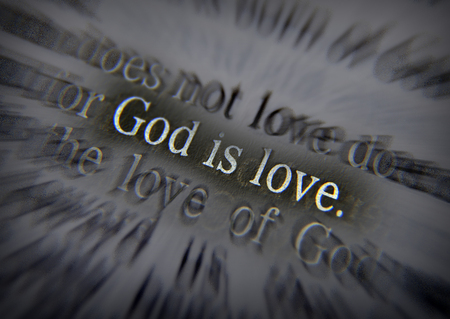 emphasize: GOD IS LOVE Bible text from 1 John 4:8, the Bible. Visual effects to emphasize the message. Macro