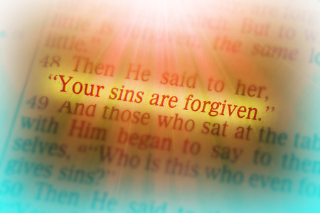 Your sins are forgiven Bible text from Luke 7:48, the Bible. Visual effects to emphasize the message. Macro Stock Photo