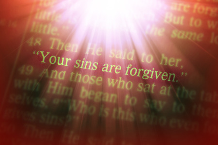 emphasize: Your sins are forgiven Bible text from Luke 7:48, the Bible. Visual effects to emphasize the message. Macro Stock Photo