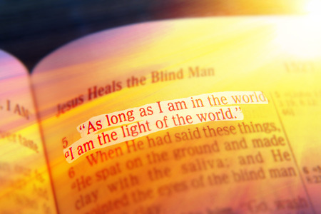 vangelo aperto: As long as I am in the world, I am the light of the world. Bible text from John 9:5, the Bible. Visual effects to emphasize the message. Macro Archivio Fotografico