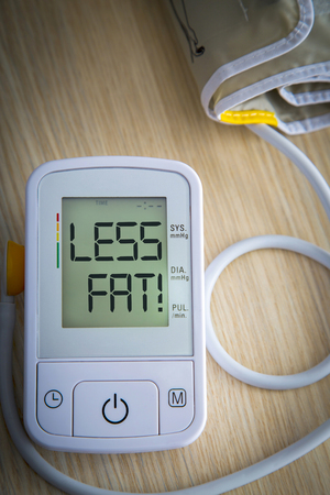 cuff: Digital blood pressure meter with warning message LESS FAT on the monitor. Health hazard concept Stock Photo