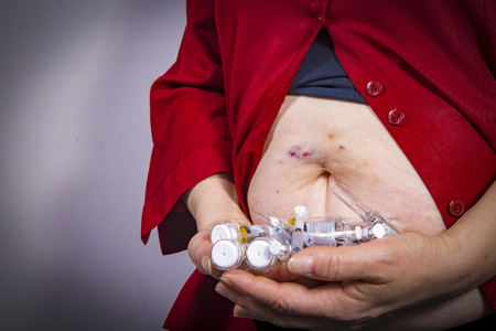Adult woman holding syringes from diabetic therapy with bruises on her stomach. Chemotherapy. Medical concept