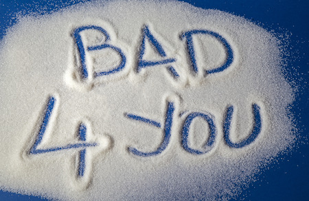 Sugar on a blue background with warning message BAD 4 YOU written on it. Health concept. Diabetes hazard Stock Photo
