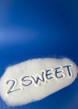Sugar on a blue background with warning message 2 SWEET written on it. Health concept. Diabetes hazard Фото со стока