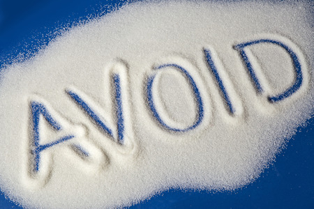 Sugar on a blue background with warning message AVOID written on it. Health concept. Diabetes hazard