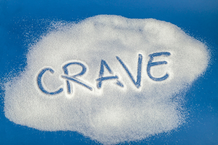 Sugar on a blue background with warning message CRAVE written on it. Health concept. Diabetes hazard Stock Photo