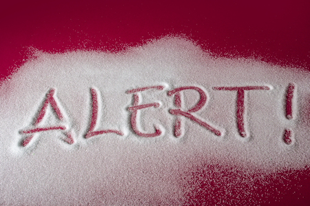 Sugar on a red background with warning message ALERT written on it. Health concept. Diabetes hazard