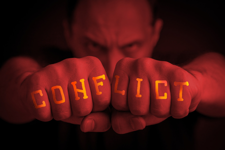 CONFLICT written on the fingers of an angry man's fists. Red colored. Message concept image.