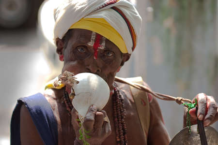 mendicant: Hindu holy man blowing a conch in south India Editorial