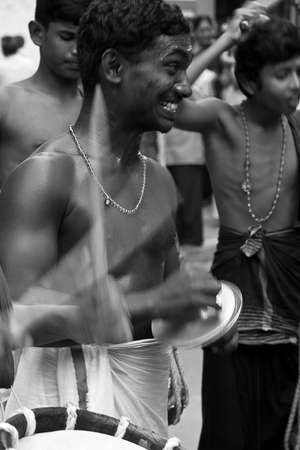cymbal: Musicians playing at a temple festival. Cymbal player in the background with drums in the foreground. The drum sticks are blurred for effect.