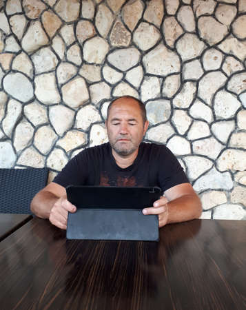 A middle-aged white man checks the route on his tablet. A man sits at a table in a cafe, against the background of a stone wall.