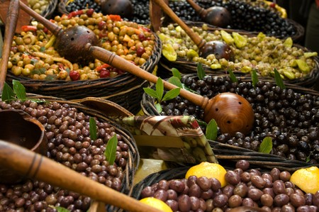 Different tastes of olives with serving spoons photo