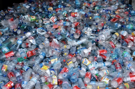 TOULOUSE, FRANCE - CIRCA 2009: Clear plastic bottles lie in a heap at an undisclosed recycling facility circa 2009 in Toulouse. The plastic is gathered by color and type to be recycled.