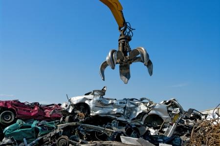 Crane picking up crushed cars
