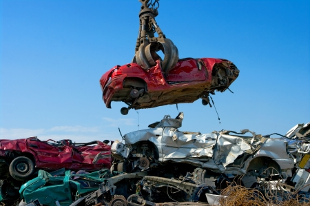junk yard: Crane picking up a car in a junkyard