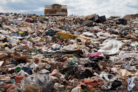 soil pollution: Truck managing garbage in a landfill site
