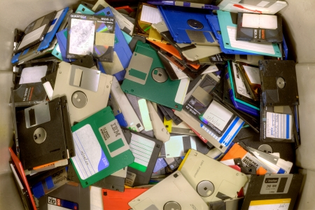 landfill site: Fairfax, Virginia - USA - 21 Novembre 2013: I diversi tipi di dischi e dischetti che si trovano in un mucchio in un impianto di riciclaggio riservate floppy usati e obsoleti. I dati potrebbero essere stati cancellati con forti magneti. Dischetti e floppy vengono triturati, poi ha incontrato