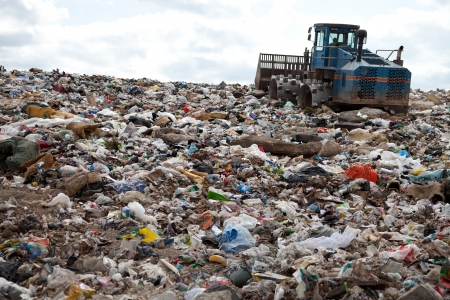 Garbage piles up in landfill site each day while truck covers it with sand for sanitary purpose Imagens
