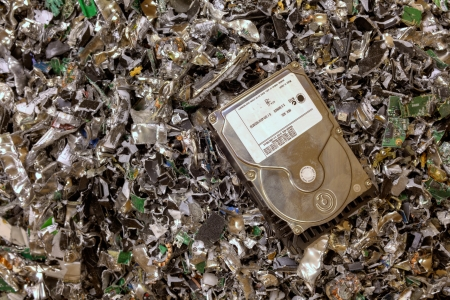A hard drive resting on a pile of shredded hard drives photo