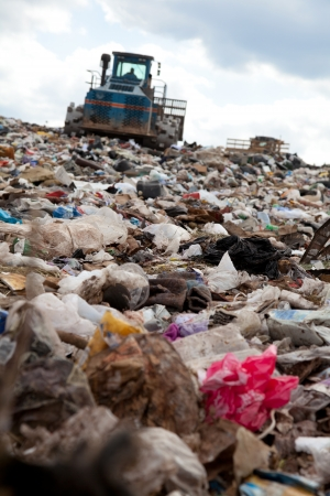 Truck moving garbage in a landfill site 스톡 콘텐츠