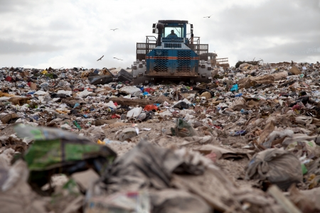 Garbage piles up in landfill site each day while truck covers it with sand for sanitary purpose 스톡 콘텐츠