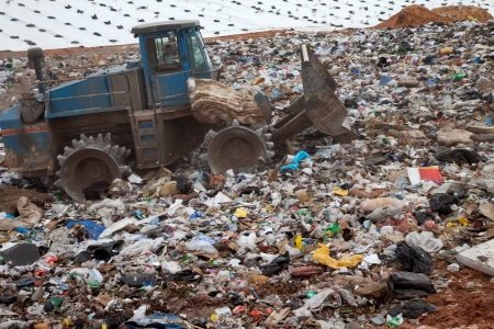 Garbage piles up in landfill site each day while truck covers it with sand for sanitary purpose photo