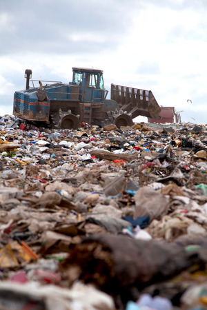 Truck flattening trash in landfill photo